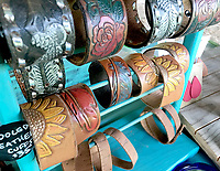 """Sally Carroll/McDonald County Press<br /> Specialty leather cuff bracelets with a western flair and inspired by nature are some of the items that Gypsy Leatherworks owner Lisa Florey offers. Florey creates bags and purses, cuff bracelets and earrings, all handcrafted and created in her studio. She currently ships orders all over the country. What is the hardest part of her job? """"Restraining myself when I go shopping for the leather,' she said, laughing."""