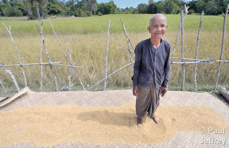 Keo Huth dries her rice in the sun in the Cambodian village of Solang Kandal.
