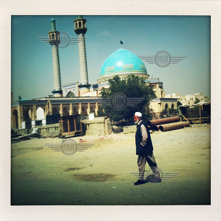 A man walks past a turquoise doomed Mosque.