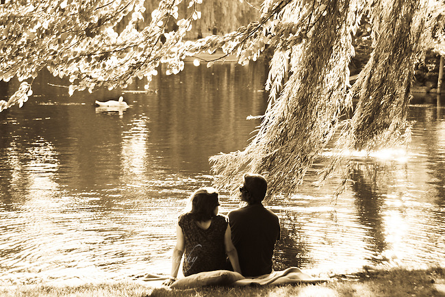 Couple sitting in sunshine on shore of pond. Sepia tone.
