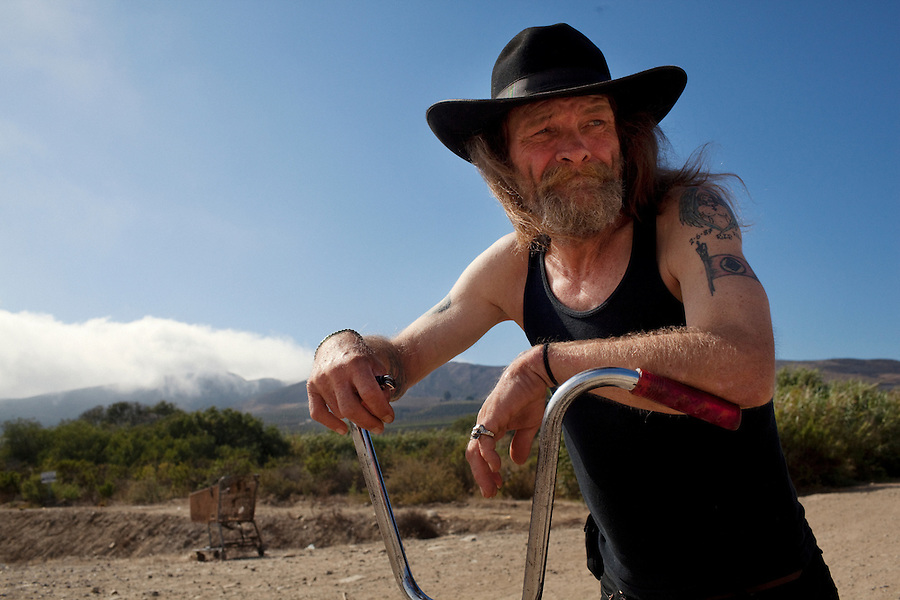 "Ventura, California, July 23, 2010 - A portrait of Tim 'Timbow' Bowman on his bike near his campsite along Ventura River bottom. Bowman has been homeless and living along the river since the early 1990's. In 1987 Bowman's 18-month-old daughter, Miranda Laurel, died from Lyme disease. His wife left him soon afterwards. A year later he fell through a plate glass window while working on a construction site, leaving him disabled and unable to work construction. He says the loss of his wife and daughter and his struggles with work sent him into a spiral. He eventually lost his home. He says he lives in the 300+ community along the river bottom because he ""feels at home."" Adding, ""I feel loved down here. Up there is nothing but trouble."" The two-mile stretch of river bottom from the Pacific to Stanley Road is home to about 300 homeless, who have carved tunnels and paths into the tall grass and bamboo. Bowman, who survives off of SSI, says, ""I lead an honest life. I don't steal, I don't rob and I share whatever I can."" .."