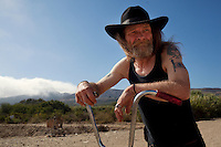 """Ventura, California, July 23, 2010 - A portrait of Tim 'Timbow' Bowman on his bike near his campsite along Ventura River bottom. Bowman has been homeless and living along the river since the early 1990's. In 1987 Bowman's 18-month-old daughter, Miranda Laurel, died from Lyme disease. His wife left him soon afterwards. A year later he fell through a plate glass window while working on a construction site, leaving him disabled and unable to work construction. He says the loss of his wife and daughter and his struggles with work sent him into a spiral. He eventually lost his home. He says he lives in the 300+ community along the river bottom because he """"feels at home."""" Adding, """"I feel loved down here. Up there is nothing but trouble."""" The two-mile stretch of river bottom from the Pacific to Stanley Road is home to about 300 homeless, who have carved tunnels and paths into the tall grass and bamboo. Bowman, who survives off of SSI, says, """"I lead an honest life. I don't steal, I don't rob and I share whatever I can."""" .."""