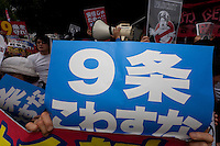 A sign supporting article 9 at a protest against the revision of article 9 of the Japanese Constitution outside the Prime-Minister's house in Kasumigasaki, Tokyo, Japan. Monday June 30th 2014. Over 10,000 people showed their support for Japan's unique peace constitution and called on the government to halt its reinterpretation of Article 9 allowing Collect Self Defence which is expected to become law on July 1st