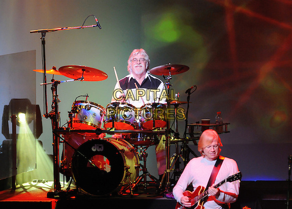 THE MOODY BLUES.Graeme Edge & Justin Hayward of The Moody Blues performs onstage at Hamilton Place during the 2010 Tour, Hamilton, Ontario, Canada..July 5th, 2010.stage concert live gig performance music half length white top full guitar drums drummer profile.CAP/ADM/BPC.©Brent Perniac/AdMedia/Capital Pictures.