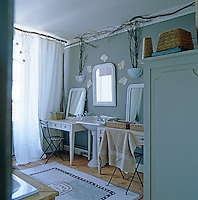 A simple country bathroom with a pair of vanity tables either side of a pedestal washbasin