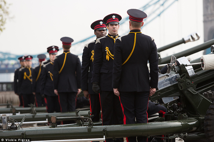 Members of the Honourable Artillery Company (HAC) stand in front of light guns as they prepare for a 62 Gun Salute in honour of Her Majesty the Queen's 88th birthday today, 21st April 2014 at the Tower of London in front of Tower Bridge in London.
