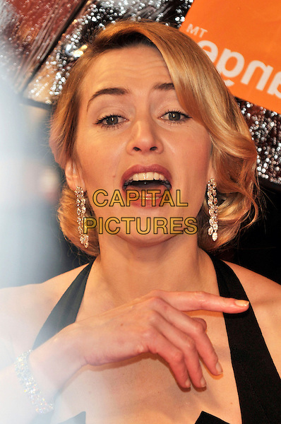 KATE WINSLET .The Orange British Academy Film Awards 2009, Royal Opera House, Covent Garden, London, England, February 8th 2009..BAFTAS arrivals portrait headshot black halterneck v diamond dangly earrings hair up mouth open funny hand finger .CAP/PL.©Phil Loftus/Capital Pictures