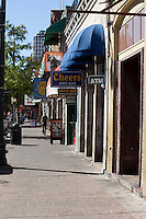 Pedestrian walks down Historic Sixth Street Austin, Texas.