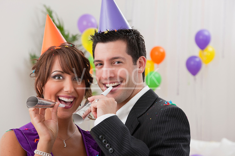 USA, Illinois, Metamora, Couple with noisemakers at New Year's Eve party