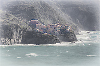 In the morning hours along the coast of the Cinque Terre, Manarola awakens by the Ligurian sea. This image of the Cinque Terre was taken from Corniglia looking across the bay. The colors of the houses perched precariously along the cliff are all different so that the fishermen can see their homes when out at sea.