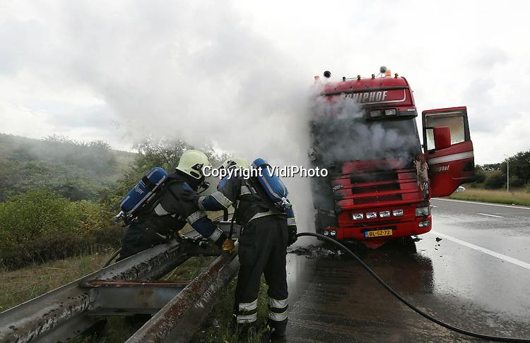 Foto: VidiPhoto<br /> <br /> RENKUM - Op de A50 bij Renkum in Gelderland is woensdagmiddag een vrachtwagen van Schiphof Bestrating uit het Drentse Nieuw Buinen uitgebrand. De oorzaak is vooralsnog onbekend. Toen de chauffeur merkte dat het in zijn cabine begon te roken, zette hij de truck bij afslag Renkum/Oosterbeek langs de kant. Ternauwernood had de man zijn voertuig verlaten, of de wagen vatte vlam. Pogingen om met behulp van een automobilist de brand te blussen mislukte, waarna via 112 hulp werd ingeroepen. De brandweer kon alleen de oplegger nog redden.