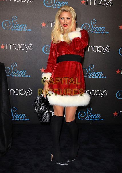 PARIS HILTON .celebrates the launch of her latest fragrance 'Siren' held At Macy's Glendale Galleria, California, USA, .3rd December 2009..full length red christmas santa mrs claus xmas outfit dress white fur fluffy trim black waistband knee high socks shoes  silver platform velvet bag hand on touching hair .CAP/ADM/KB.©Kevan Brooks/Admedia/Capital Pictures