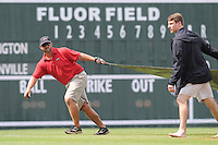 Head groundskeeper Greg Burgess of the Greenville Drive helps remove the tarp following a rain delay before a game with the Lexington Legends on Sunday, July 21, 2013, at Fluor Field at the West End in Greenville, South Carolina. Lexington won, 2-0. (Tom Priddy/Four Seam Images)