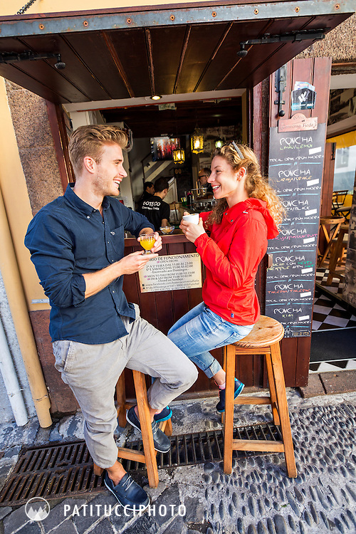 A couple having drinks at a small bar in Funchal, the capitol city of Madeira Island