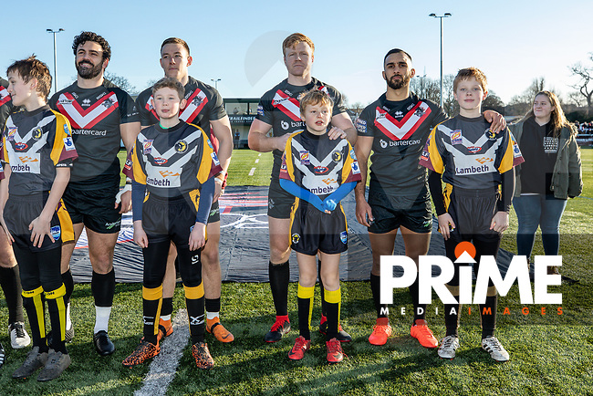 London Broncos players with mascots ahead of the Betfred Super League match between London Broncos and Wakefield Trinity at Castle Bar , West Ealing , England on 3 February 2019. Photo by David Horn.