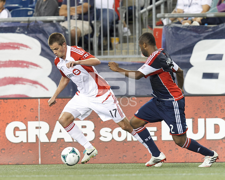 Toronto FC substitute forward Justin Braun (17) brings the ball forward as New England Revolution defender Andrew Farrell (2) defends. In a Major League Soccer (MLS) match, Toronto FC (white/red) defeated the New England Revolution (blue), 1-0, at Gillette Stadium on August 4, 2013.