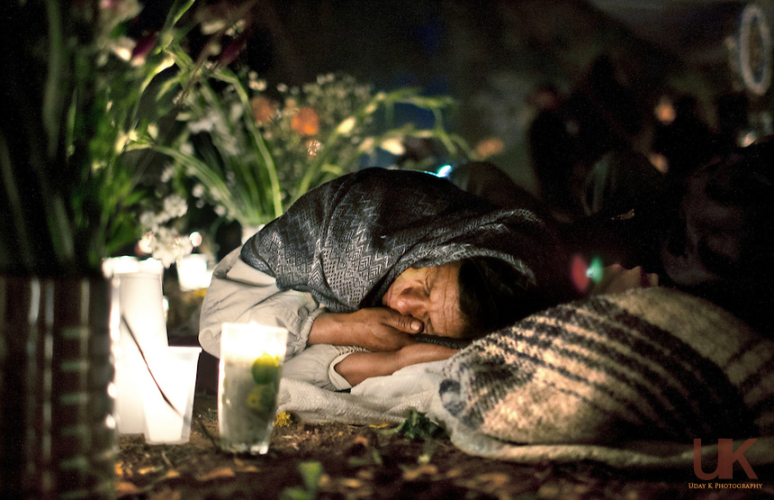 After a busy day of celebration, woman sleeps next her husband's grave.