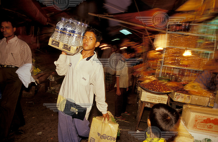 Boy selling bottled water in market.