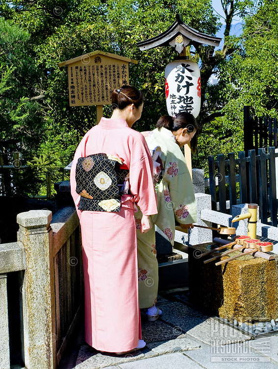 Two Japanese women in traditional kimono visit a temple in Kyoto, Japan.