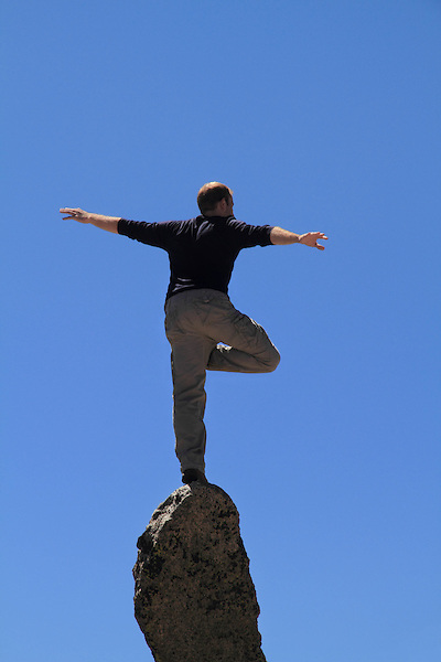 Man balancing on a granite spire on Mount Evans (14,264 ft), Idaho Springs, Colorado. Guided photo tours and hiking tours to Mt Evans.