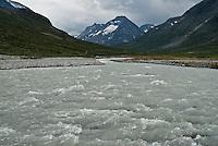 Glacial river flowing through mountains of Jotunheimen national park near Spiterstulen, Norway