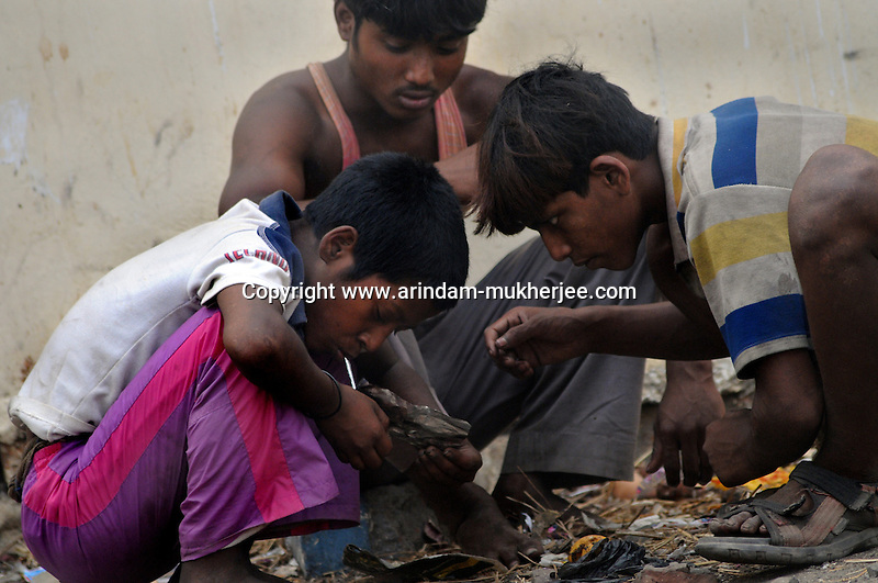 Alamgir and his friends taking brown sugar at the Sealdah railway premises. He got addicted to drugs after he came to Sealdah. He ran away from his home due to domestic violence and poverty. As per his version his father was a drunkard and used to beat his mother for no reason. His father even could not earn enough money to buy food for their big family. Due to this traumatic situation he ran away from house at the age of seven. Ever since, the Sealdah railway station in Kolkata has been his home. As far as company is concerned, he had not much reason to miss his family. There are around 500 children, from 5 to 16 years, who live in the premises of Kolkata's second largest train terminus. Most of them addicted to Brown Sugar and sniffing industrial adhesive Dendrite. They say they don't feel hungry if they take the drugs. Their presence is conspicuous, even in a place that registers an average footfall of 1.4 million on weekdays. Their activities cover a wide range, from begging, to pulling handcarts, to petty theft, to selling odds and ends on the platform or on trains. The money, earned or ill-gotten as the case may be, is spent in procuring heroin, brown sugar, cocaine, and tubes of Dendrite. Calcutta, West Bengal, India. Arindam Mukherjee