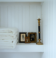 Three miniature framed portraits are propped on a shelf in the bathroom next to a pile of fresh white towels and an antique brass candlestick