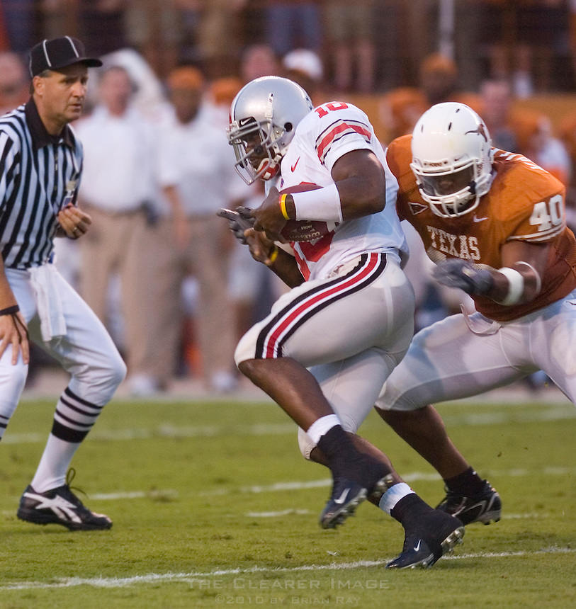 09 September 2006: Ohio State quarterback Troy Smith (#10) dodges a tackle by Texas defender Robert Killebrew (#40) during the  Buckeyes 24-7 victory over the Longhorns at Darrell K Royal Memorial Stadium in Austin, TX.