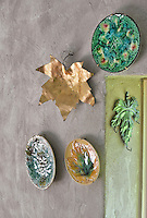 Three ceramic plates with a leaf motif, a gold leaf shaped ornament and a green ceramic leaf hang on a stone wall.
