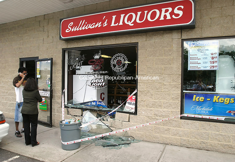 WATERBURY, CT 7/17/07- 071707BZ01-Umesh Naraine, left, talks on the phone as Smita Bhagat, surveys the damage after an SUV crashed through the wall at Sullivan's Liquors on Bank Street in Waterbury Tuesday.  Several bricks were knocked loose, the window was smashed and dozens of bottles inside were thrown about in the accident.<br /> Jamison C. Bazinet Republican-American