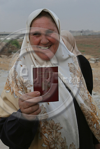 Palestinian women hold their passport after they returned from Egypt into Gaza Strip through Erez crossing 29 July 2007 in Beit Hanun, northern Gaza Strip. Around 100 of the thousands of Palestinians stranded in Egypt crossed into Israel on their way to Gaza today, but many left behind said they were barred for their political beliefs. Egypt and Israel yesterday agreed that 627 of the 6,000 stranded Palestinians, who have been living in increasingly dire conditions, would be allowed back to the Gaza Strip, with 100 crossing today and 527 tomorrow.