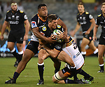 Sharks player Louis Schreuder (C) is tackled by Brumbies players during the Super Rugby match between the ACT Brumbies and the South African Sharks in Canberra on March 17, 2018. AFP PHOTO / MARK GRAHAM --- IMAGE RESTRICTED TO EDITORIAL USE - STRICTLY NO COMMERCIAL USE --
