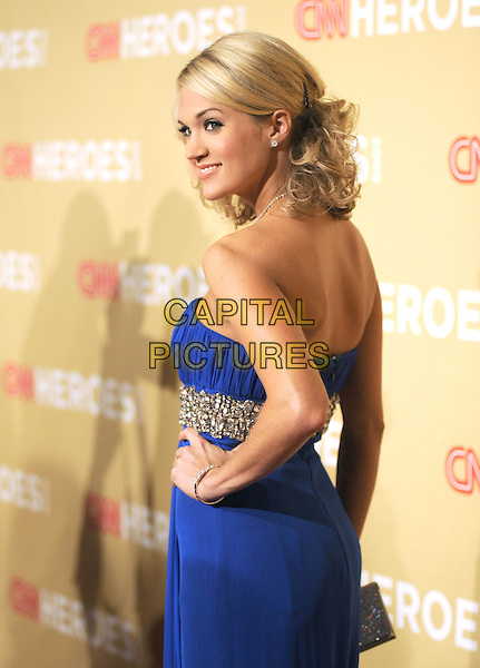 CARRIE UNDERWOOD .at The 3rd Annual CNN Heroes: An All-Star Tribute held at The Kodak Theatre in Hollywood, California, USA,  November 21st 2009                                                                   .half length strapless blue dress necklace gown gold jewel encrusted empire waistband embellished beaded side profile hand on hip looking over shoulder back rear behind .CAP/RKE/DVS.©DVS/RockinExposures/Capital Pictures