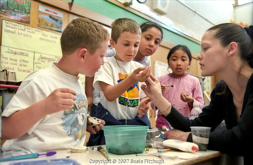 """In science class, a Dinosaur Unit in elementary school comes alive for the children as they search for teacher-made """"prehistoric"""" specimans in bowls of soil."""