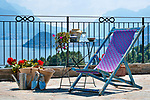 A terrace in Menaggio with a small iron table, flowers, straw basket, and blue espadrilles with a view of Lake Como, Italy and Bellagio in the background