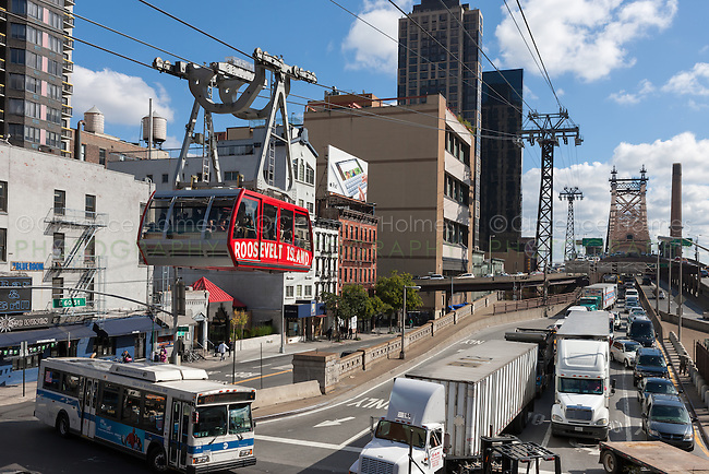 Mid-day traffic enters Manhattan on the Queensboro Bridge, which spans the East River between the boroughs of Manhattan and Queens in New York City, while the Roosevelt Island Tram leaves the station for Roosevelt Island located in the East River.