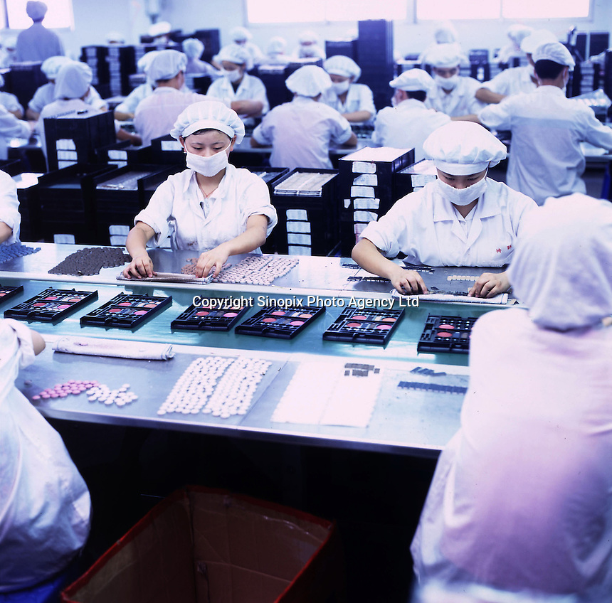 Workers work on a production line that produces lipstick, mascara and other cosmetics at a factory in the Pear River Delta in Fu Yong, near the Shenzhen Special Economic Zone in China..24-JAN-03