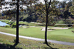 A path through a forested area and around golf course greens and pond surrounded by multi floored condos in Branson Missouri