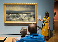 NWA Democrat-Gazette/CHARLIE KAIJO Museum Educator Kim Crowell of Rogers asks attendees to think of what the painting &quot;Along The River&quot; By William Trost <br />Richards reminds them of as Tom and Sue O'Neal of Bella Vista watch at the Crystal Bridges museum in Bentonville, AR on Monday, September 11, 2017. Creative Connections is a program for individuals in the early stages of Alzheimer&acirc;&euro;&trade;s or dementia and their care partners. Museum Educators facilitate interactive discussions of artworks in the galleries, followed by hands-on art activities in the studio. The discussions on the works are designed to stimulate memories and emotions between Alzheimer's patients and their caretakers.