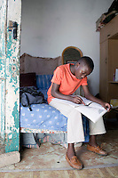 CAPE TOWN, SOUTH AFRICA - MARCH 15: Sikhumbuzo Hlahleni, age 15, a student at Cape Town City Ballet's youth company does his geography homework in his family house on March 15, 2010 in Khayelitsha, South Africa. He trains in Cape Town every Saturday. He also trains a few days week at home in Khayelitsha, a poor township outside Cape Town. He has to change taxi three times to get to the school. (Photo by Per-Anders Pettersson For Stern Magazine).
