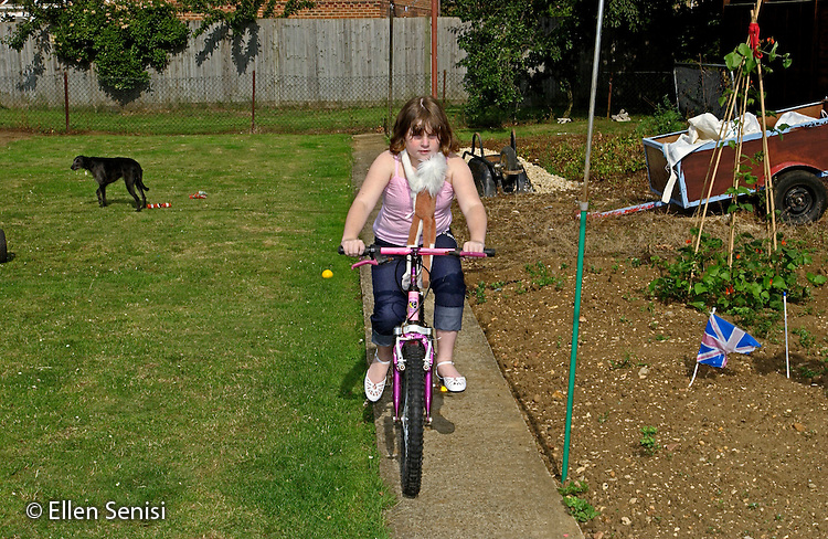 MR / Radley, Abingdon, Oxfordshire, England.Girl (9) rides her bicycle in her backyard..MR: Web2.©Ellen B. Senisi