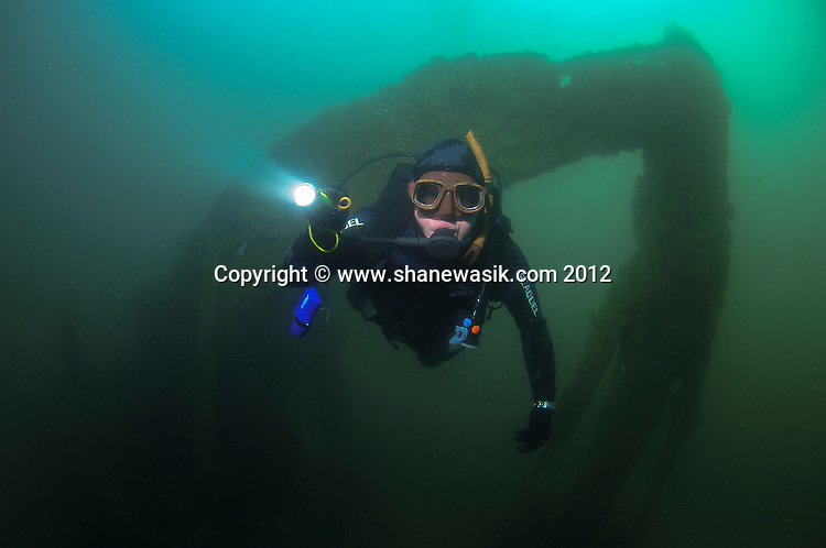 A diver swims through the resting arm of the digger wreck.
