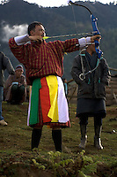 An archer takes aim during a three-day inter-village archery contest at Gangtey in the Phobjika Valley of Bhutan. Archery is the national sport of Bhutan and the traditional course is 150m long. The coloured strips of cloth tucked into the archer's waistband indicate how many times he has hit the target in the course of the competition.