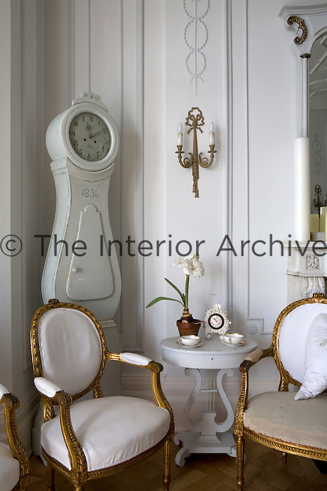 A pair of gilded Gustavian carver chairs either side of a side table and a Mora clock in the corner of the living room