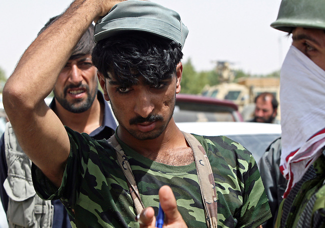 A private security guard near the Maiwand district bazaar in Kandahar province, Afghanistan is questioned about whether he fired his gun during a three-way battle with Taliban insurgents about an hour earlier. A Canadian soldier was killed in the exchange, and the shot was initially believed to have come from the convoy. An official investigation later found that the fatal bullet had come from the Taliban. Aug. 9, 2008. DREW BROWN/STARS AND STRIPES