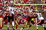 San Francisco 49ers quarterback Jeff Garcia (5) passes ball as Chicago Bears defensive tackle Keith Traylor (94) and defensive end Alex Brown (96) rush him on Sunday, September 7, 2003, in San Francisco, California. The 49ers defeated the Bears 47-7.