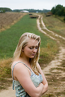 Blonde woman in blue-green dress standing on dirt road through field