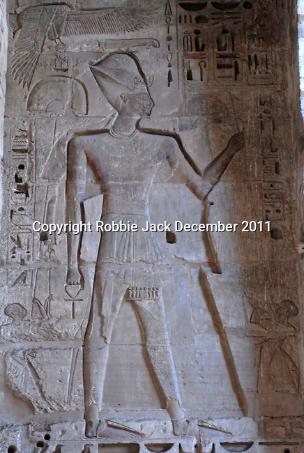 """Wall releif of Ramses III in a Portico with Hypostyle in the second forecourt at the mortuary temple of Ramses III at Medinet Habu at Thebes.Thebes was the ancient capital of Egypt and was built in and around modern day Luxor.The ancient name for Medinet Habu was Djamet meaning """"males and mothers."""" Its holy ground was believed to be where the Ogdoad,the four pairs of primeval gods,were buried.Medinet Habu was both a temple and a complex of temples.Queen Hatshepsut who ruled Egypt from 1479-1458 BC  and Tuthmosis III who reigned from 1479-1425 BC built a small temple to Amun on the site of an earlier structure. Next to their temple, Ramses III who reigned from 1186-1155 BC built his mortuary temple.He then enclosed both structures within a massive mud-brick enclosure.The temple precinct measures about 700 feet by 1000 feet and contains more than 75,350 sq ft of decorated surfaces across its walls.It is the best preserved of all the mortuary temples of Thebes."""