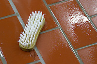 cleaning brush on the tiled winery floor dom m picard chateau de ch-m chassagne-montrachet cote de beaune burgundy france