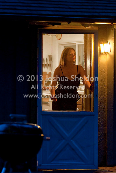 Young woman standing at screen door, looking out